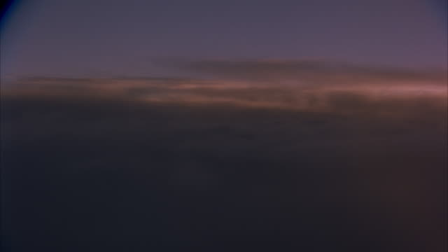 AERIAL OF SKY WITH THICK LAYER OF CLOUDS ON BOTTOM HALF OF FRAME. SEE PEACH COLORED TINT OF SUNLIGHT. PURPLE SKY.