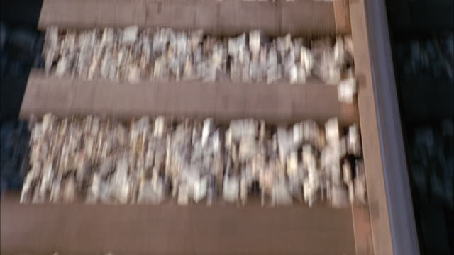MEDIUM ANGLE OF RAILROAD TRACKS PASSING QUICKLY BENEATH CAMERA. SEE HORIZANTAL WOODEN BOARDS ON TRAIN TRACKS. SEE GRAVEL ON EITHER SIDE.
