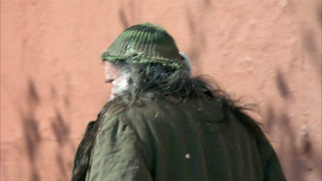 MEDIUM ANGLE OF HOMELESS MAN WITH WHITE BEARD AND TATTERED CLOTHING WALKING FROM LEFT TO RIGHT, TRACKS HOMELESS WOMAN AS SHE WALKS FROM LEFT TO RIGHT.