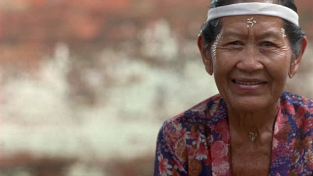 CLOSE ANGLE OF OLDER WOMAN WEARING FLORAL PRINT TOP OR DRESS AND WHITE HEADBAND. WOMAN LOOKING AT CAMERA, OCCASIONALLY SMILES OR SPEAKS TO SOMEONE OFFSCREEN. ELDERLY PEOPLE.