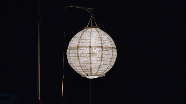 MEDIUM ANGLE OF ILLUMINATED WHITE PAPER SPHERICAL LANTERN. ROUND SPHERE LANTERN HANGING FROM THIN WOOD POST.