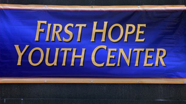 WIDE ANGLE OF SIGN OR BANNER THAT READS FIRST HOPE YOUTH CENTER. COMMUNITY CENTER.