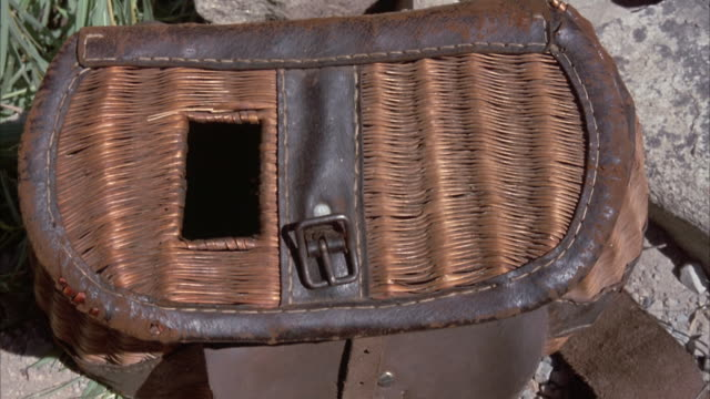 CLOSE ANGLE OF WICKER BASKET, CREEL, WITH FISH INSIDE, PROBABLY AFTER FISHING. HAND FROM LEFT OPENS BASKET, SEE FISH INSIDE, THEN CLOSES.