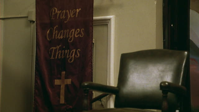 WIDE ANGLE OF RELIGIOUS BANNER HANGING ON WALL NEXT TO LEATHER CHAIR. CRUCIFIX AND TEXT ON BANNER. PRAYER CHANGES THINGS. COULD BE CHURCH OR COMMUNITY CENTER.