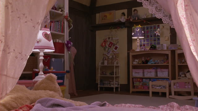 MEDIUM ANGLE POV FROM THE INSIDE OF A CHILD'S FORT BUILT OVER A YOUNG GIRL'S BED. LOOKS LIKE IT COULD JUST BE CURTAINS.  THE WALLS OF THE BEDROOM ARE DECORATED WITH MANY PINK DECORATIONS.  A STUFFED ANIMAL ON THE BED.
