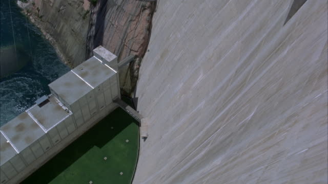 HIGH ANGLE DOWN OF GLEN CANYON DAM. SEE WATER, SMALL BUILDING, GRASS.