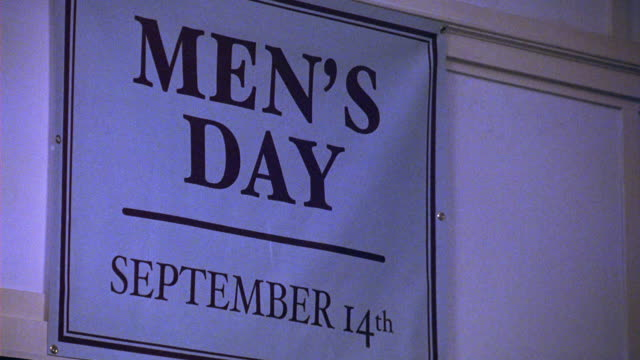 UP ANGLE OF SIGN ON WALL WITH TEXT MEN'S DAY AND SEPTEMBER. COULD BE COMMUNITY CENTER OR SOCIAL CLUB.