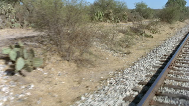 MEDIUM ANGLE OF RAILROAD TRACKS PASSING QUICKLY BENEATH CAMERA. SEE HORIZANTAL WOODEN BOARDS ON TRAIN TRACKS. SEE GRAVEL AND GREEN BUSHES TO SIDE OF TRAKCS. COULD BE IN DESERT REGION.