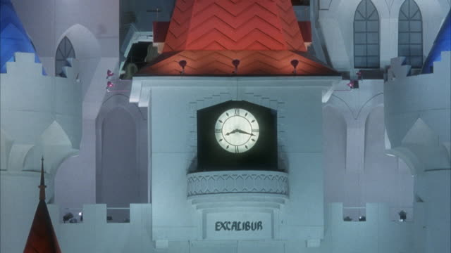 CLOSE ANGLE OF CLOCK TOWER AT EXCALIBUR HOTEL, PANS UP TO TOP OF LEFT SPIRE.