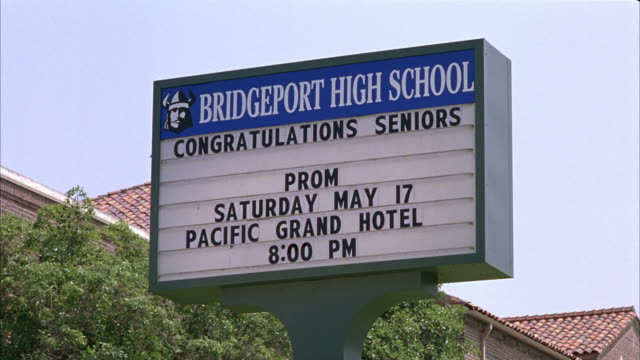 CLOSE ANGLE OF SIGN: BRIDGEPORT HIGH SCHOOL/CONGRATULATIONS SENIORS/ PROM/ SATURDAY MAY 17/ PACIFIC GRAND HOTEL/ 8:00 PM. BRICK BUILDING WITH TILE ROOF OR HIGH SCHOOL IN BG.