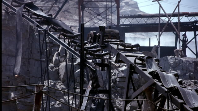 MEDIUM ANGLE OF MINE. SEE MINERS OR WORKERS USING OLD WOODEN MINE EQUIPMENT. TWO MINERS WORK ON TURNING AN OVERSIZED WHEEL. SMALL BRIDGE RUNS ACROSS ROCKY MINE. BLUE SKY IN THE BACKGROUND.