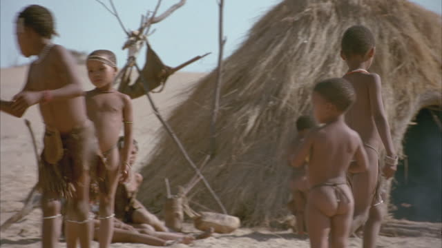 MEDIUM ANGLE OF NATIVE CHILDREN PLAYING IN CIRCLE OF GRASSY HUTS. THEY ARE WEARING LOINCLOTHS AS THEY PLAY WITH A BALL, TOSSING IT BACK AND FORTH. THEY SKIP TO A BEAT WITH SMILES ON THEIR FACES.