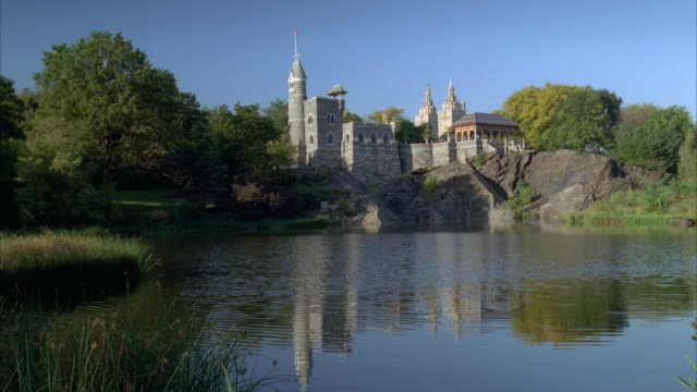 WIDE ANGLE OF BELVEDERE CASTLE ON  ROCK CLIFF BY LAKE IN CENTRAL PARK. SMALL AMERICAN FLAG FLAPS ON TOP OF SPIRE, DOCK OR WALKWAY VISIBLE AT RIGHT. STONE BUILDING.