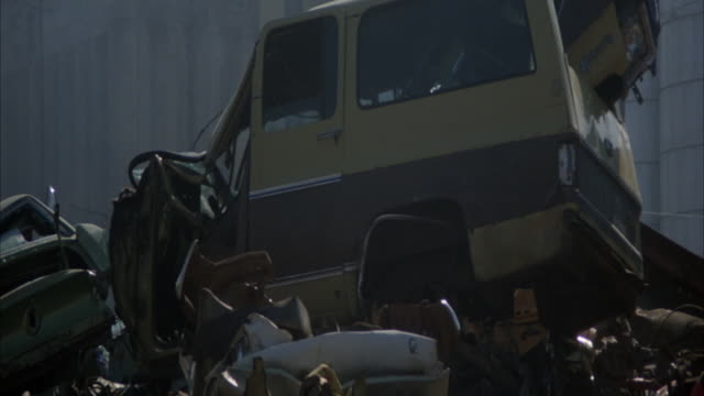 MEDIUM ANGLE OF DEMOLISHED CARS PILED UP IN JUNKYARD OF SCRAP YARD. SHOT PANS RIGHT THROUGH PILES OF CARS.