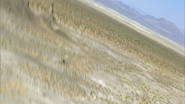 AERIAL BACK PILOT POV BANKING RIGHT AND LEFT ON ARID AREA OR DESERT WITH MOUNTAIN SPIRES. TRONA PINNACLES.