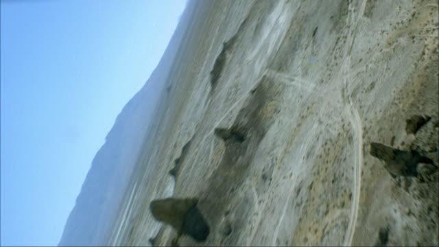 AERIAL PILOT POV OF ARID AREA OR DESERT WITH MOUNTAIN SPIRES. NEG CUT. TRONA PINNACLES.