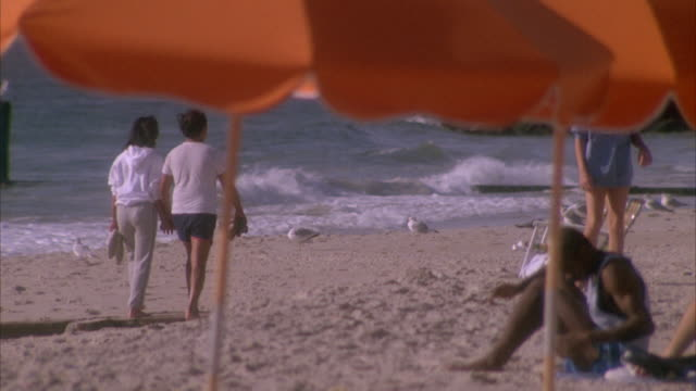 MEDIUM ANGLE OF COUPLE WALKING HAND IN HAND ALONG BEACH. SEE MAN AT RIGHT SITTING UNDERNEATH UMBRELLA. SEE PARTIALLY BLOCKED ORANGE UMBRELLAS IN FOREGROUND.