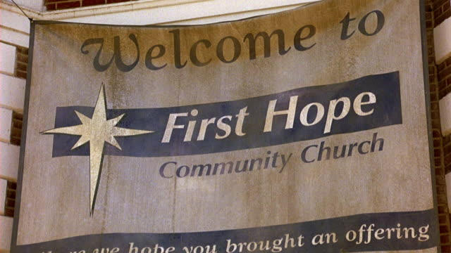 UP ANGLE OF BANNER HANGING ON CORNER OF BRICK BUILDING THAT READS WELCOME TO FIRST HOPE COMMUNITY CHURCH, WHERE WE HOPE YOU BROUGHT AN OFFERING. CHURCH, COMMUNITY CENTER, OR RELIGIOUS BUILDING.