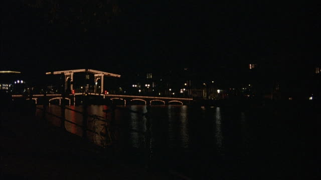 WIDE ANGLE OF BRIDGE OVER CANAL AT NIGHT. SEE GAZEBO TYPE BUILDING IN MIDDLE OF BRIDGE LIT UP. POV FROM SIDE OF CANAL.