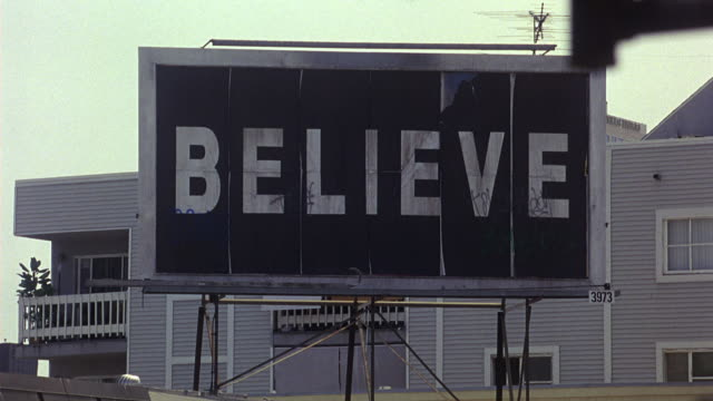 PAN DOWN FROM BILLBOARD IN URBAN AREA THAT READS BELIEVE TO BUILDING SIGN THAT READS FIRST HOPE FAMILY COMMUNITY CENTER.  SIGN IN WINDOW READS EACH ONE REACH ONE. RELIGIOUS BUILDING OR CHURCH.