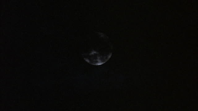 STATIC CLOSE UP SHOT OF FULL MOON IN SKY WITH DARK OMINOUS-LOOKING CLOUDS PASSING OVER IT. FULL MOON IS OUT OF FOCUS.