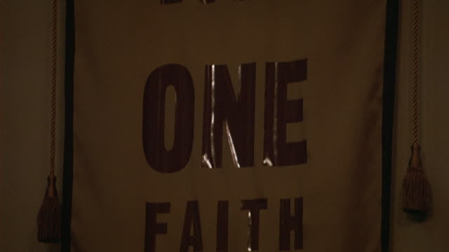 PAN DOWN OF BANNER TEXT THAT READS ONE LORD, ONE FAITH, ONE BAPTISM. RELIGIOUS. COULD BE CHURCH OR COMMUNITY CENTER.