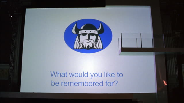 WIDE ANGLE OF MOVIE SCREEN WITH PROJECTION WHAT WOULD YOU LIKE TO BE REMEMBERED FOR? WRITTEN BENEATH A CLIPART VIKING EMBLEM. COULD BE MEMORY VIDEO FOR HIGH SCHOOL DANCE OR CELEBRATION.