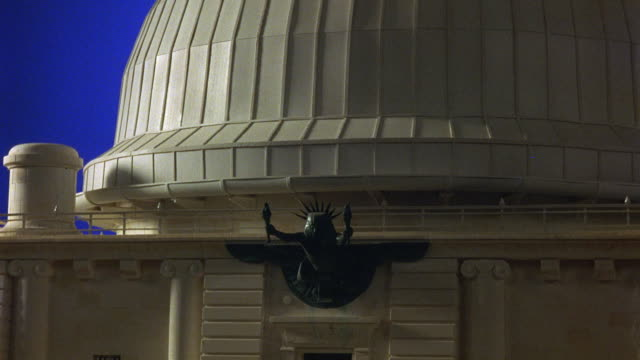 MEDIUM ANGLE OF MINIATURE MODEL OF FRONT OF OBSERVATORY, PART OF DOME IS VISIBLE AND AT CENTER IS BRONZE STATUE  AT ROOFLINE OF A MAN WITH A SPIKED CROWN HOLDING TORCHES ALOFT. BLUE SCREEN.