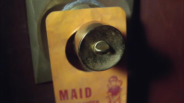 CLOSE ANGLE OF DIRTY BRASS DOORKNOB. PLASTIC TAG HANGS FROM DOORKNOB, READS MAID. HAND GRABS DOORKNOB AND ATTEMPTS TO OPEN DOOR.