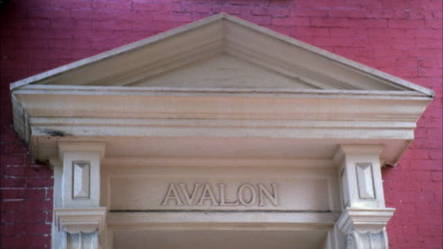 MEDIUM ANGLE OF PEDIMENT ABOVE ENTRANCE OR DOOR. AVALON WRITTEN UNDER PEDIMENT. WALLS OF BUILDING ARE BRICK.