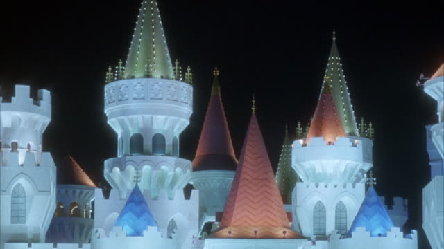 CLOSE ANGLE OF CASTLE TOP SPIRES OF EXCALIBUR HOTEL LIT IN DIFFERENT COLORS. BEAUTY SHOT.