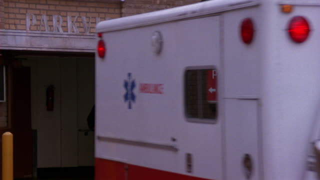 MEDIUM ANGLE OF HOSPITAL WITH AMBULANCE PARKED IN FRONT. AMBULANCE TURNS ON LIGHTS, THEN EXITS TO RIGHT. SIGN ABOVE ENTRANCE READS PARKVIEW AND ANOTHER READS EMERGENCY PARKVIEW HOSPITAL.