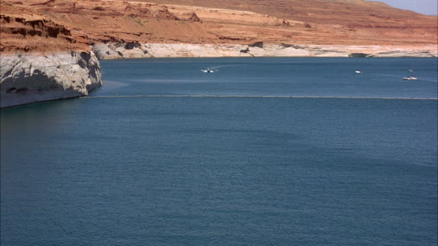 WIDE ANGLE OF LAKE POWELL SURROUNDED BY RED ROCK CANYON. FA SEE BOATS OR HOUSEBOATS IN FROM DISTANCE.