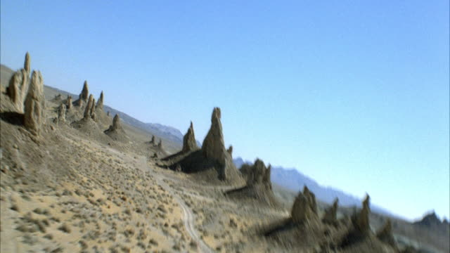 AERIAL OF ISOLATED DESERT AREA WITH MOUNTAIN SPIRES. FLYING POV.