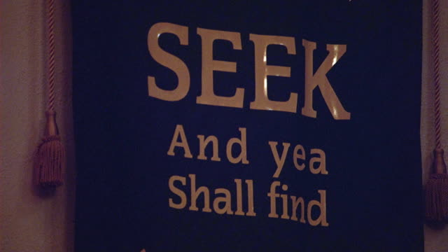 PAN UP OF BANNER IN CHURCH, COMMUNITY CENTER, OR RELIGIOUS BUILDING.  BANNER TEXT READS KNOCK AND THE DOOR SHALL BE OPENED UNTO YOU, SEEK AND YEA SHALL FIND, AND ASK AND IT SHALL BE GIVEN UNTO YOU.