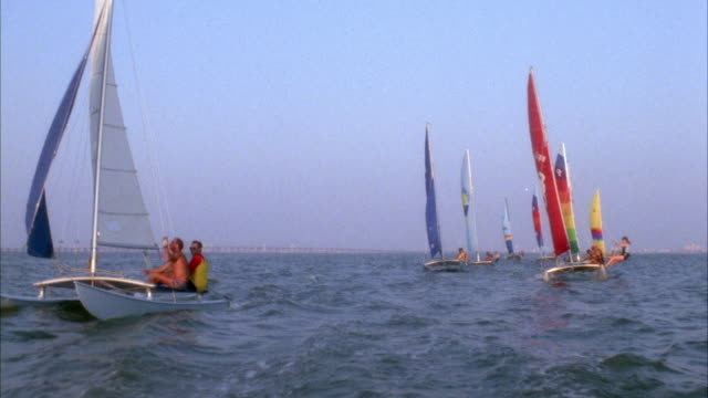 MEDIUM ANGLE STRAIGHT BACK MOVING POV OF HANDFUL OF CATAMARANS SAILING FORWARD IN OCEAN, MOST LIKELY DURING RACE.