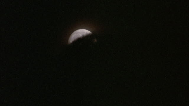 STATIC CLOSE UP SHOT OF FULL MOON IN SKY WITH DARK OMINOUS-LOOKING CLOUDS PASSING OVER IT.