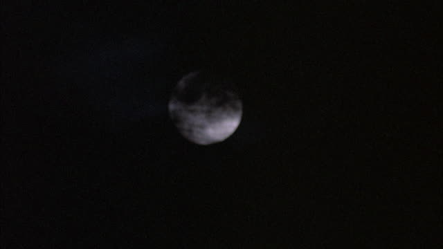 STATIC CLOSE UP SHOT OF FULL MOON IN SKY WITH DARK OMINOUS-LOOKING CLOUDS PASSING OVER IT. FULL MOON IS OUT OF FOCUS AND OVERALL SHOT SHOWS A SHAKING MOTION.