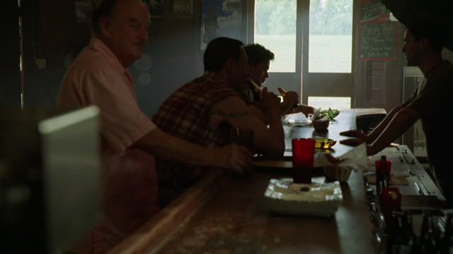 MEDIUM ANGLE OF MEN SITTING AT BAR OR PUB, DRINKING BEERS AND EATING. COULD BE RESTAURANT.