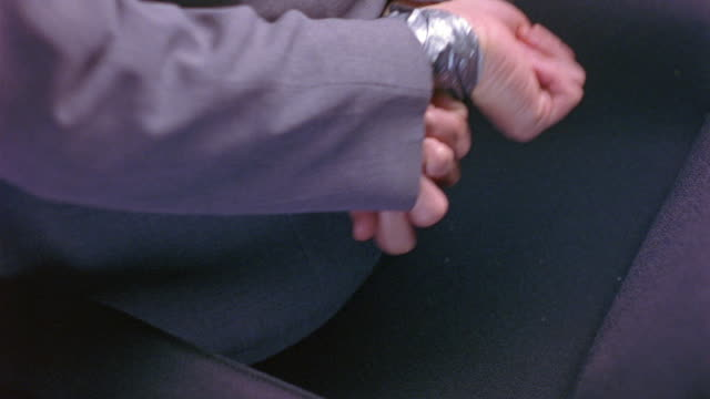 MEDIUM ANGLE OF HANDS OF HUMAN BODY DUCT TAPED TOGETHER LIKE HAND CUFFS. PERSON WEARS BLUE OR GRAY SUIT. HANDS STRUGGLE TO GET FREE UNTIL HAND OF OTHER MAN RELEASES HANDS FROM TAPE. COULD BE HOSTAGE OR KIDNAPPING.