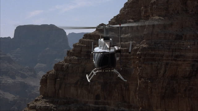 AERIAL TRACKING SHOT OF TAIL END OF HELICOPTER FLYING OVER GRAND CANYON. COLORADO RIVER BELOW.