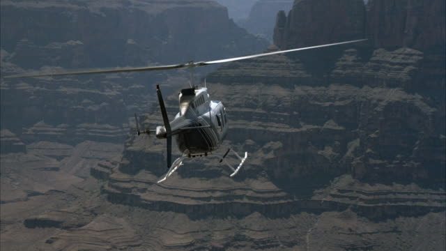 AERIAL TRACKING SHOT OF TAIL END OF HELICOPTER FLYING OVER GRAND CANYON. SEE COLORADO RIVER BELOW.