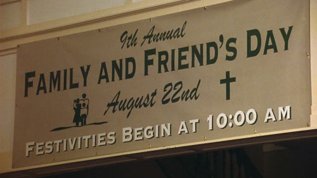 UP ANGLE OF POSTER OR BANNER IN CHURCH, COMMUNITY CENTER, OR RELIGIOUS BUILDING. SIGN READS 9TH ANNUAL FAMILY AND FRIEND'S DAY, AUGUST 22ND, FESTIVITIES BEGIN AT 10:00 AM. CRUCIFIX SYMBOL ON POSTER.