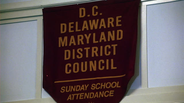 UP ANGLE OF SIGN OR BANNER HANGING ON WALL THAT READS D.C. DELAWARE MARYLAND DISTRICT COUNCIL AND SUNDAY SCHOOL. COULD BE CHURCH, COMMUNITY CENTER, OR RELIGIOUS BUILDING.