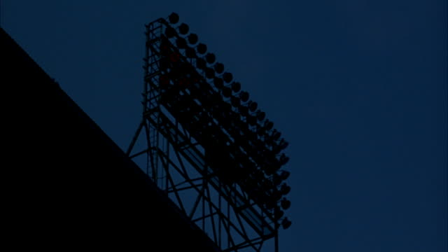 MEDIUM UP ANGLE OF STADIUM LIGHTS. POV UNDER OVERHANG. LIGHTS SLOWLY LIGHTS UP, BULB FLASHES, THEN GOES OUT.
