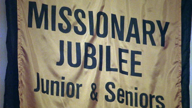 UP ANGLE OF BANNER OR SIGN IN CHURCH, COMMUNITY CENTER, OR RELIGIOUS BUILDING THAT READS MISSIONARY JUBILEE, JUNIORS & SENIORS, AUGUST 4TH.