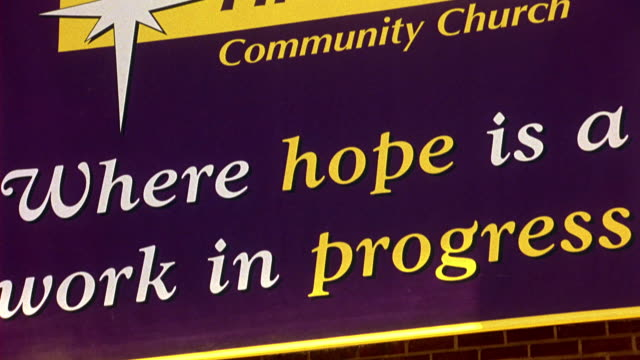PULL BACK FROM BANNER ON BRICK BUILDING THAT READS FIRST HOPE COMMUNITY CHURCH, WHERE HOPE IS A WORK IN PROGRESS. GOES OUT OF FOCUS AT END OF SHOT. CHURCH, COMMUNITY CENTER, OR RELIGIOUS BUILDING.