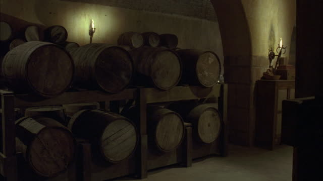 MEDIUM ANGLE OF DIM LIT WINE CELLAR, BASEMENT. SEE BROWN OAK WINE BARRELS STACKED AGAINST WALL. SEE TORCHES IN BACKGROUND.