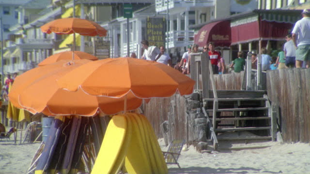 MEDIUM ANGLE OF PEOPLE WALKING ALONG BEACH BOARDWALK. SEE STAIRS DOWN TO SAND. SEE ORANGE UMBRELLAS.