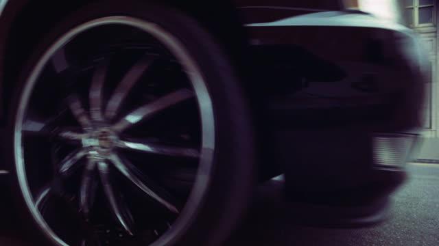 MEDIUM ANGLE OF GRILL, HOOD, AND WHEEL OF CADILLAC ESCALADE SUV AS IT DRIVES FORWARD ON CITY STREET. CHROME WHEEL.
